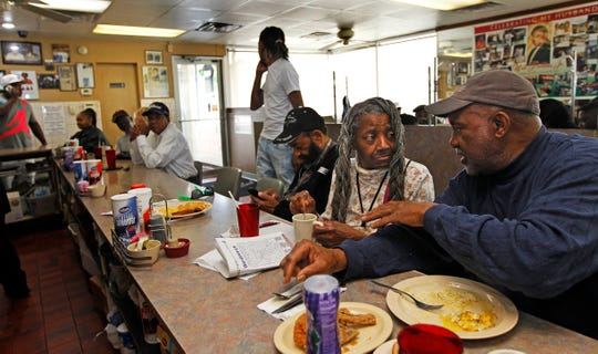 Jerry Smith, 69, right, talks with a community activist who goes only by the name Ms. Rose, while having breakfast on Thursday at  Mr. Perkins  Family Restaurant. Smith has been dining at the restaurant for 50 years. Like many of the regular customers, Smith and Rose frequent the restaurant several times a week.
