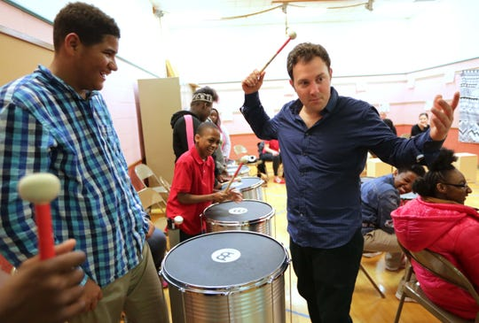 Wisconsin Conservatory of Music instructor Mitch Shiner, right, works with Gaenslen School students including Jervonta Terry, left, and Javon Glass, center, both eighth graders, during an adaptive learning drumming class conducted by the Wisconsin Conservatory of Music at Gaenslen School in Milwaukee.