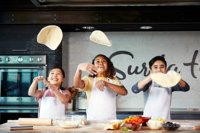 Teens toss pizza dough in a Sur La Table cooking class.