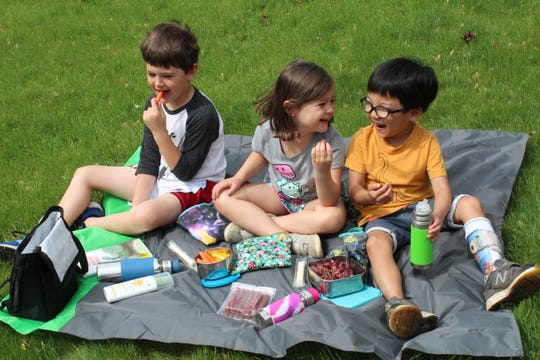 Corban, Mara and Haddon Sherwood share lunch and laughs on a summer picnic.