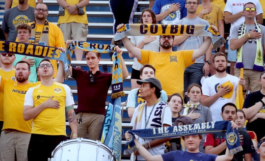 Some Nashville SC fans hold up their scarves during the anthem before the start of the U.S. Open Cup between Nashville SC and  Charleston Battery on Wednesday, May 29, 2019, at the Dean A. Hayes Track and Soccer Stadium at MTSU.