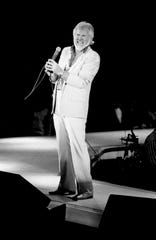 Kenny Rogers grimaces as he tries for a high note before for the audience at the MTSU's Murphy Center Nov. 3, 1984. He is co-starring with Crystal Gayle and country-rock band Sawyer Brown.