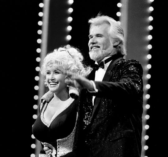 "Host Kenny Rogers, right, joins Dolly Parton after she opens the 18th annual CMA Awards show Oct. 8, 1984 with her current hit, ""Tennessee Homesick Blues."""