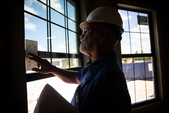Structural building inspector Tim Stick checks windows as he conducts a framing inspection on the site of a new home on Winding Cypress Drive in Naples on Thursday, May 30, 2019.
