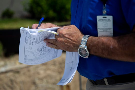 Structural building inspector Tim Stick writes a note as he conducts an inspection on the site of a new home on Winding Cypress Drive in Naples on Thursday, May 30, 2019.