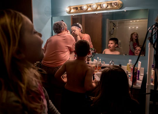 Seated in the sink of the bathroom she shares with her sister, Jenna, Jazmin calmly applies her make-up for prom while her younger siblings wreak havoc in the bathroom around her.