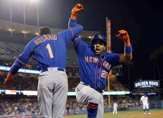 New York Mets' Dominic Smith (22) celebrates his solo home run with Amed Rosario (1) during the seventh inning of the team's baseball game against the Los Angeles Dodgers on Wednesday, May 29, 2019, in Los Angeles.