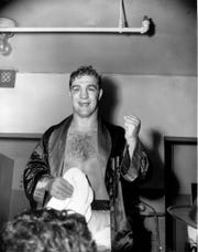 Rocky Marciano holds up one of his fists used to score the technical knockout over Joe Louis in 8th round of their non-title fight at Madison Square Garden in New York City, Oct. 26, 1951. Marciano was one of many famous fighters to train in the area.