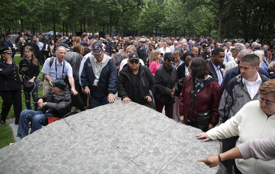 "People gather around stones that are part of a new memorial glade at ground zero after a dedication ceremony in New York, Thursday, May 30, 2019. Former New York City Mayor Michael Bloomberg says the new memorial glade at the World Trade Center site ""helps us fulfill our duty"" to those who were sickened or died after responding to the Sept. 11 attacks. (AP Photo/Seth Wenig)"