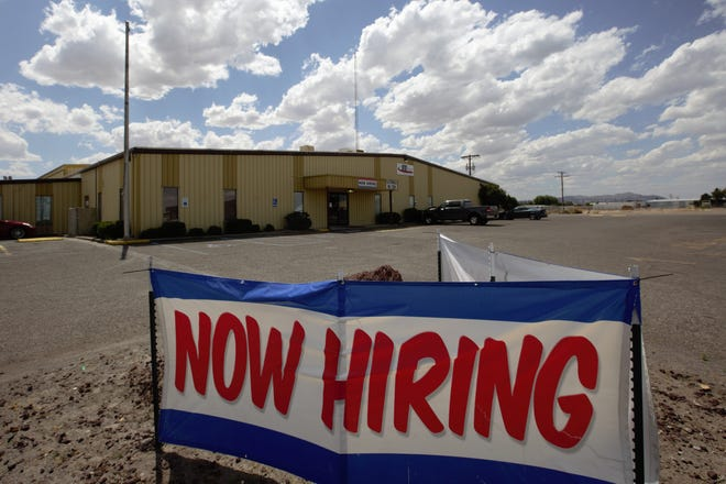 "A ""now hiring"" sign in front of the headquarters of STS of New Mexico's Las Cruces headquarters in May 2019. As many workers find themselves laid off during the coronavirus pandemic, a few businesses are still hiring, including Walmart."
