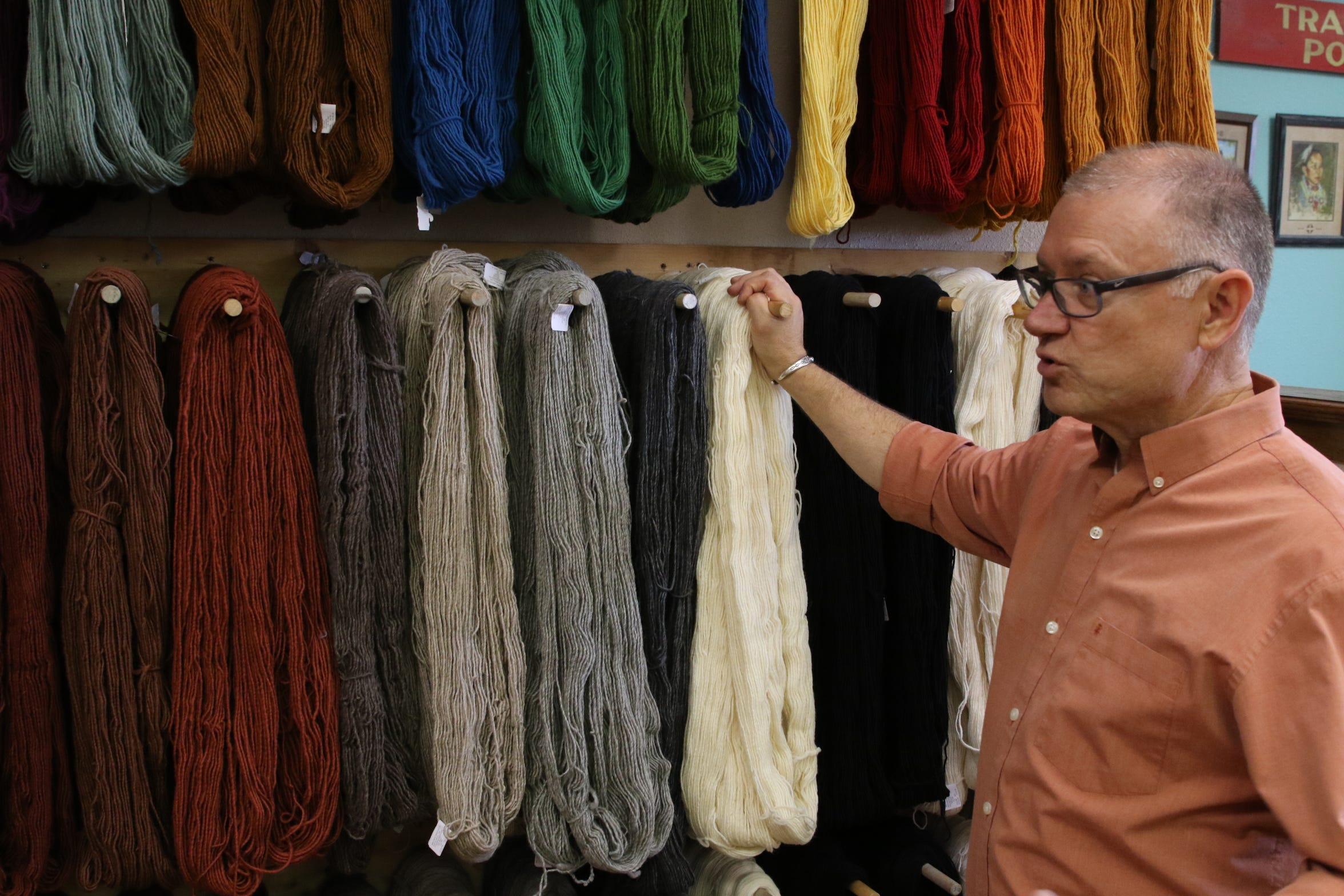 Owner Kent Morrow talks about the many shades of dyed wool offered for sale at his Shiprock Trading Post in Farmington.