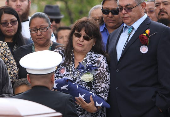 State Sen. John Pinto's youngest daughter, Karen Arviso, center, receives her father's flag after the funeral Mass on May 30 at Sacred Heart Cathedral in Gallup.