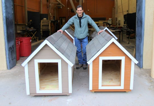 Construction Trades instructor at Ruidoso High School Lonnie Jossart, stands next to his student's last quarter project. The dog houses were donated to the Humane Society and four adopters will be given the houses.