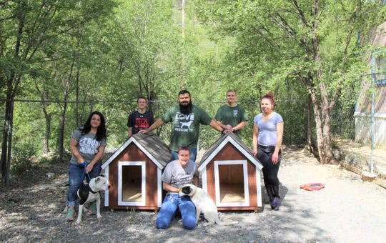 Freckles and Dixie, two adoptable dogs at the Humane Society of Lincoln County shelter pose for a picture with two  of the four dog house built by student of the Trades Construction class at Ruidoso high. Four adopters will receive a dog house and the adoption fees will be waived for the first four dog adopters.