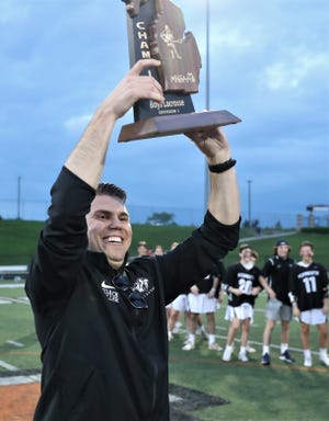 Plymouth coach Ray Miller lifts up the regional championship trophy after his team beat Saline 19-12.