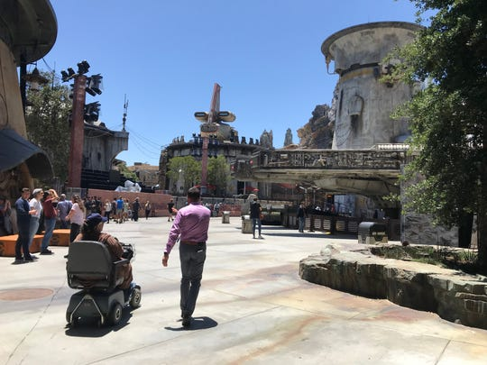 Guests enter Star Wars: Galaxy's Edge at Black Spire Outpost on planet Batuu where a full-size Millennium Force (right) awaits its new crew. Star Wars: Galaxy's  Edge opens Friday, May 31, 2019, at Disneyland in Anaheim.
