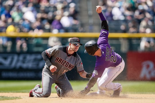 May 30, 2019; Denver, CO, USA; Colorado Rockies shortstop Trevor Story (27) is tagged out by Arizona Diamondbacks shortstop Nick Ahmed (13) attempting to steal second base in the fourth inning at Coors Field. \