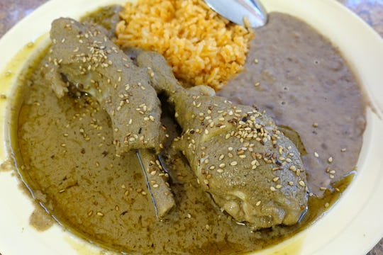 Pipian verde with chicken leg, pork rib, beans and rice at El Rincon Poblano in Phoenix.