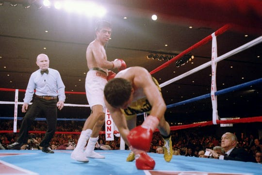 Michael Carbajal (left) stands by as his opponent Chiquita Gonzales falls to the canvas during their bout at the Las Vegas Hilton in Las Vegas in 1993.