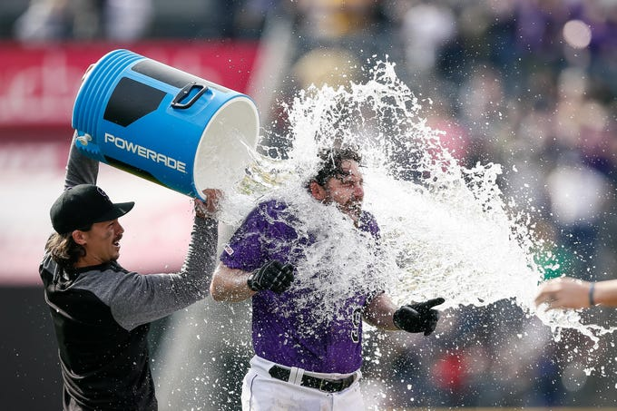 May 30, 2019; Denver, CO, USA; Colorado Rockies catcher Tony Wolters (14) douses first baseman Daniel Murphy (9) after his walk off single in the tenth inning against the Arizona Diamondbacks at Coors Field.