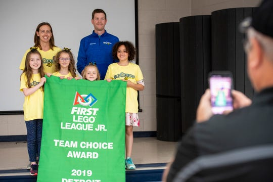 Memphis BeeCoders coaches Heather Ager, back left, and Josh Mills, back right, pose for a photo with members of the team and the banner they received Wednesday, May 29, 2019 after an assembly at Memphis Elementary School. Last month, the team competed in the FIRST World Championships in Detroit, where they were chosen by their peers at the competition for the Team Choice Award, for teams that best display the core values of FIRST Robotics.