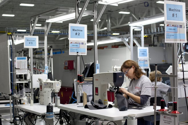 Employees work sections of leather trim components on sewing machines on at Eissmann Group Automotive in Port Huron in 2015.