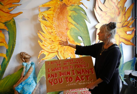 Amy Trompetter holds a sign with a quote from Greta Thunberg beside a puppet in her likeness at the Redwing Blackbird Theater in Rosendale on May 15, 2019. Thunberg is a Swedish student who has been protesting about the need for action on climate change.