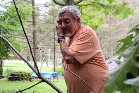Gary Wolf, of North Codorus Township, wipes sweat from his face as he removes branches from a tree that fell into his yard, on Thursday, May 30, 2019.