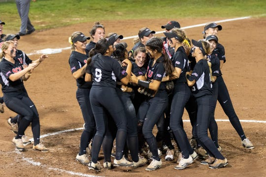 Southern Oregon players storm the field after winning the NAIA National Championship.