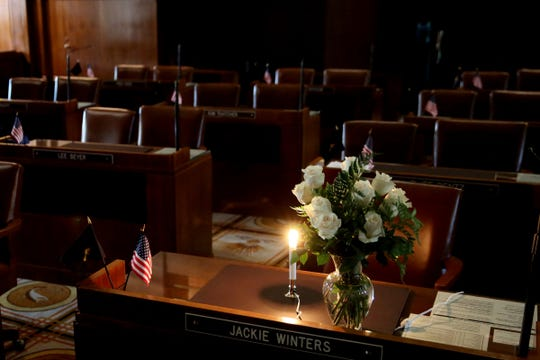 Roses and a single light are left on the desk of Sen. Jackie Winters in the darkened Senate Chambers at the Oregon State Capitol in Salem on May 29, 2019. Winters, the first African American to ever serve in the Legislature as a Republican rose to the position of Senate Republican leader, was 82.