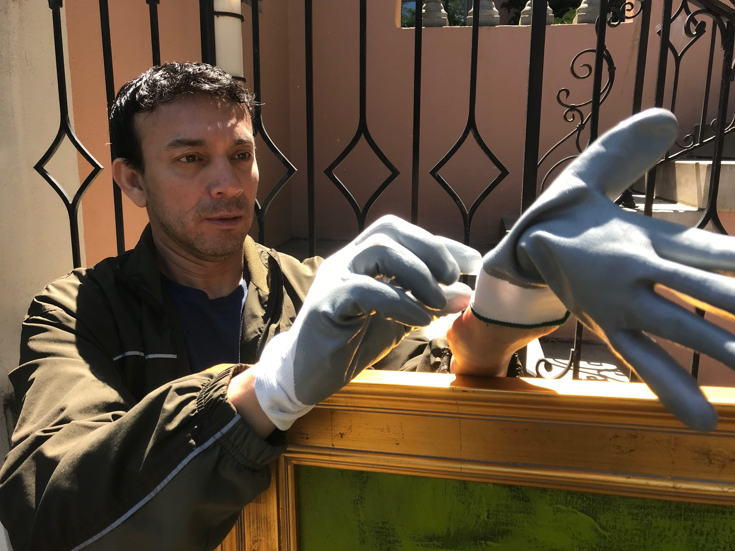 San Angelo artist René Alvarado puts on special gloves before picking up art to be installed in the European Union May 15, 2019.