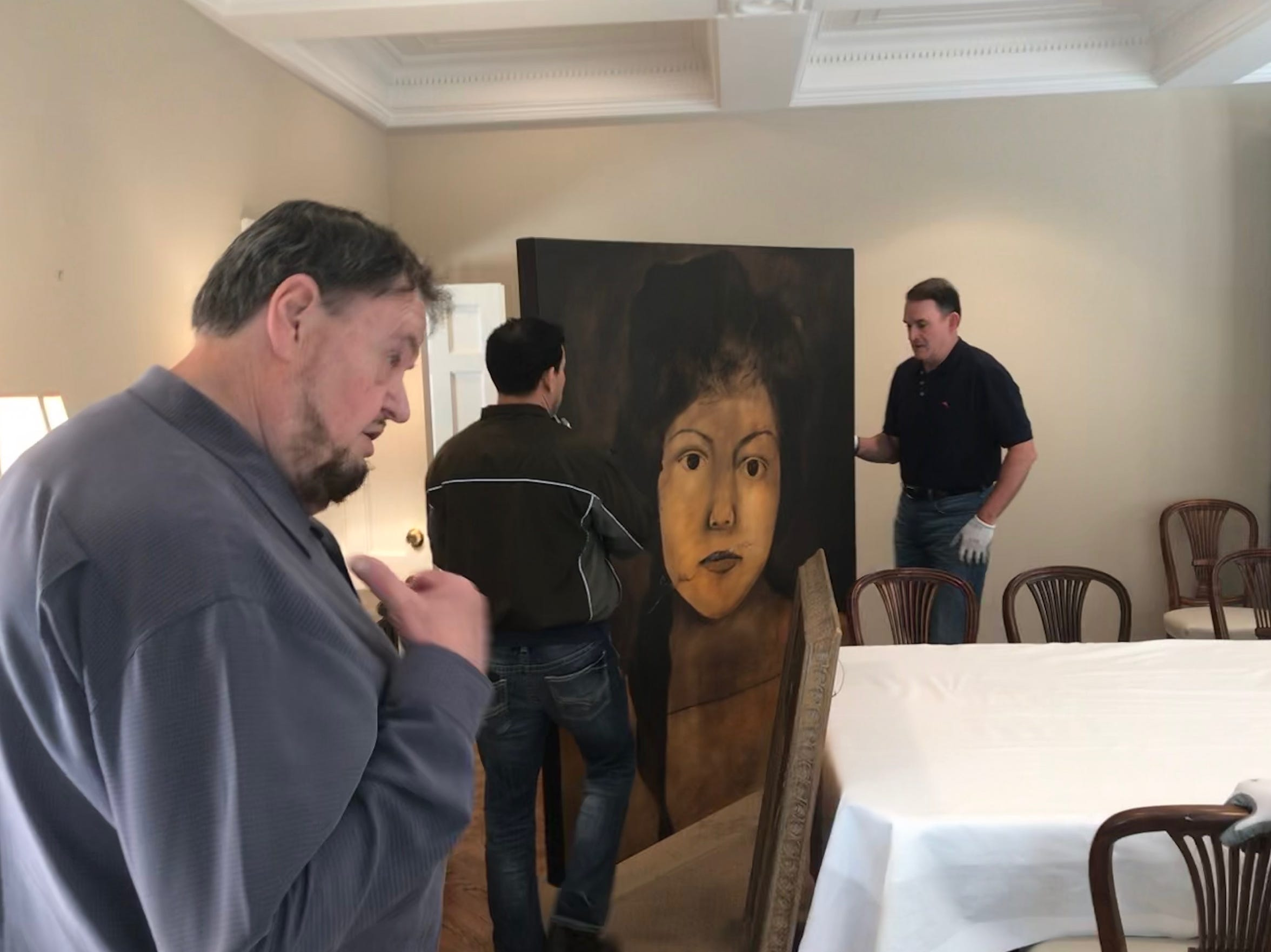 San Angelo Museum of Fine Arts Director Howard Taylor advises René Alvarado and Jeff Curry on where to hang a painting in the European Union residence, May 15, 2019.