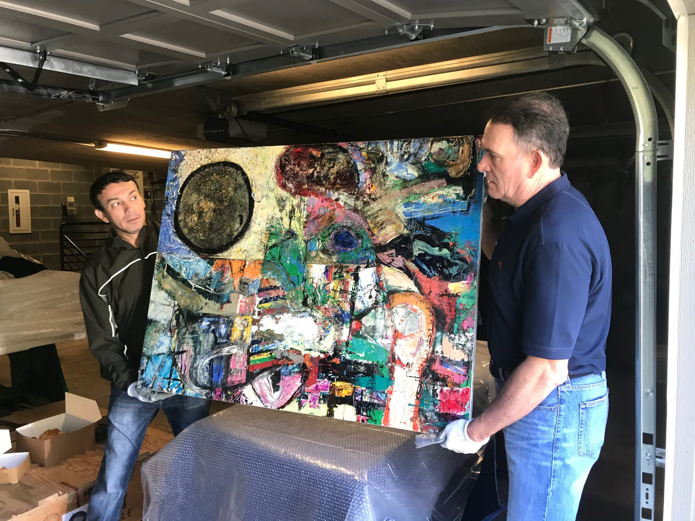San Angelo artist René Alvarado and SAMFA board member Jeff Curry pick up a painting to be installed in the European  Union residence on May 15, 2019.