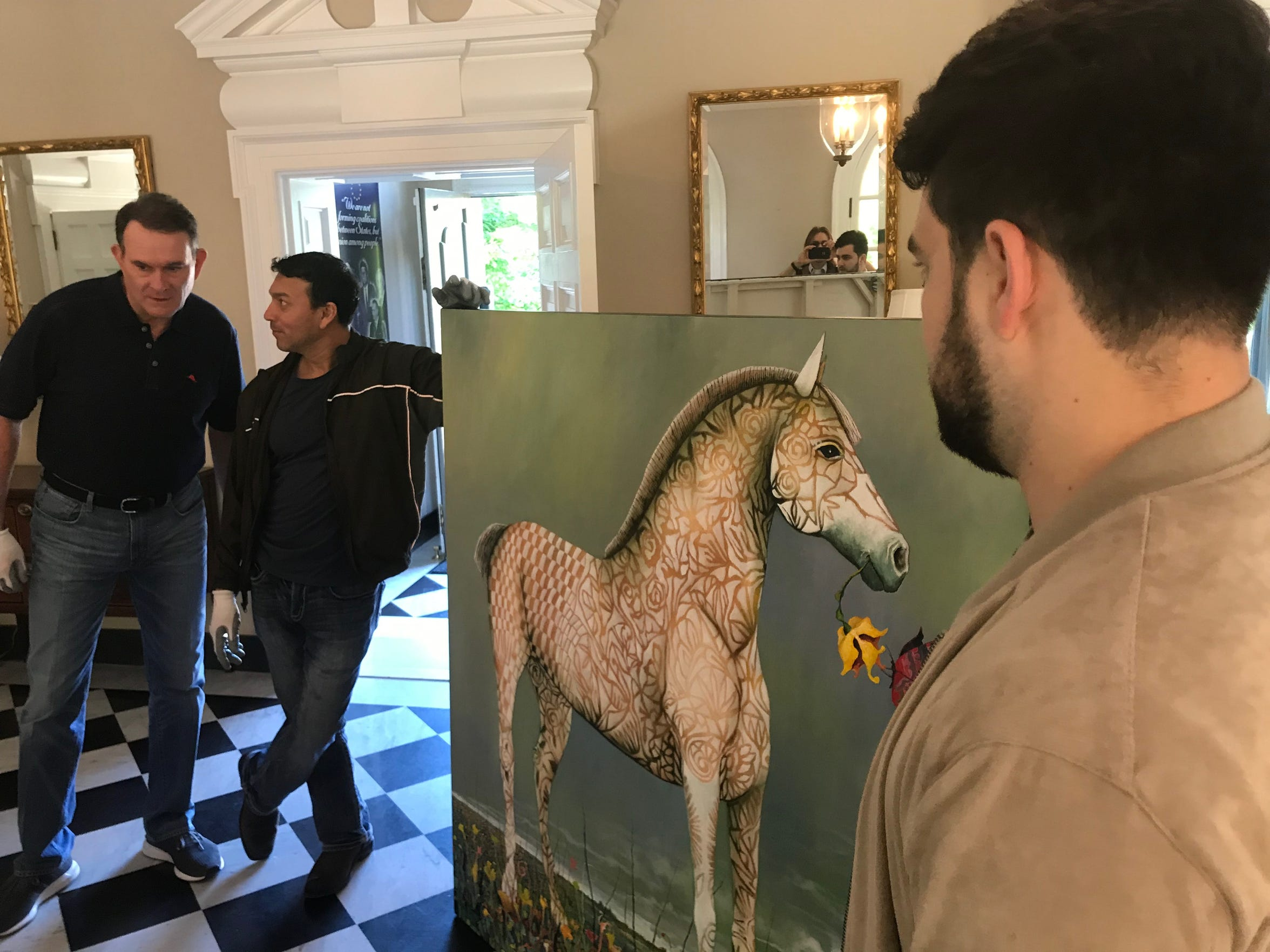 Left to Right: SAMFA board member Jeff Curry, San Angelo artist René Alvarado, and volunteer Taylor Velarde pause while carrying a painting into the European Union residence on May 15, 2019. The art is on loan from the San Angelo Museum of Fine arts until May 2020.