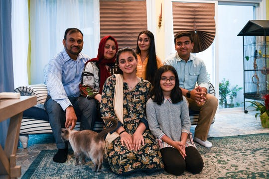 The Aziz family poses in their home in Salisbury.