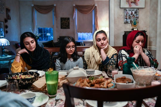 Rayyan, Safeerah and Armeen Aziz (left to right) pray with their mother Hina Siddiqui before breaking their fast at the nights iftar at their home in Salisbury.