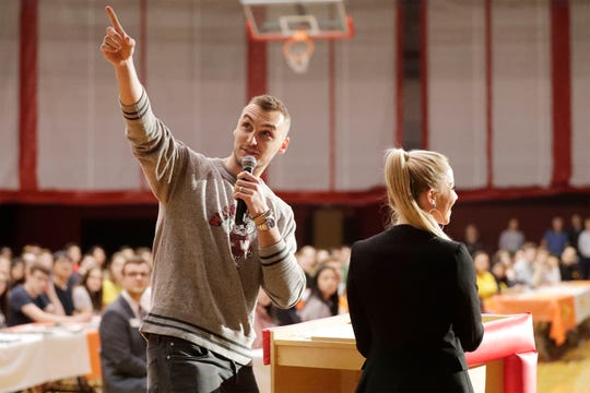 Sheboygan's Sam Dekker, left, points out a projection on the screen by his wife Olivia Harlan Dekker while emceeing the first Sheboygan South Senior Signing Day, Thursday, May 30, 2019, in Sheboygan, Wis. Senior Signing Day is designed to recognize our seniors and their next steps in college and career.
