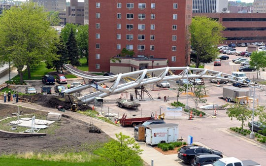 Workers construct the first half of the Arc of Dreams sculpture Thursday, May 30, on the Big Sioux River in Sioux Falls.