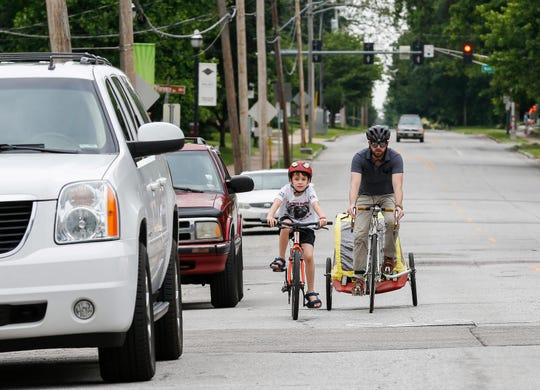Cody Stringer and his son Vaughan Stringer, 8, ride their bikes down Walnut Street on Tuesday, May 28, 2019.