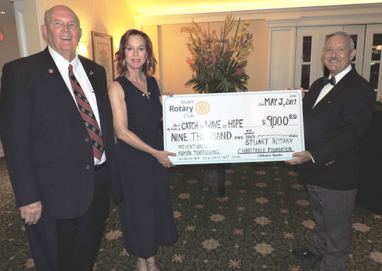 Stuart Rotary Club President Dr. Bruce Irwin, left, and Dave Dyal, right, chair of the Stuart Rotary Charitable Foundation, present Lynne Barletta of Catch the Wave of Hope with a check for $9,000 at the third annual Mayors' Gala at Mariner Sands Country Club in Stuart.