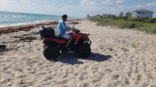 Ryan Chabot of Inwater Research Group in Jensen Beach marks on a GPS where a new sea turtle nest was laid the night before. The turtle crawled through a thick line of dying Sargassum seaweed to make her nest.