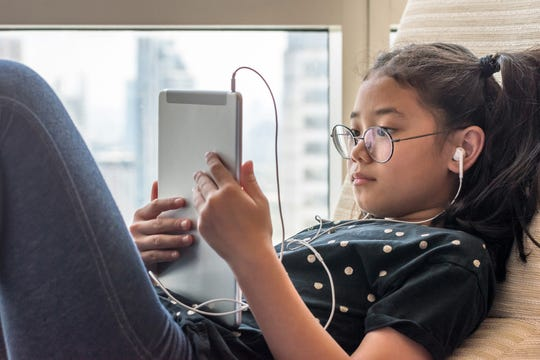 A student uses a technology device at home.