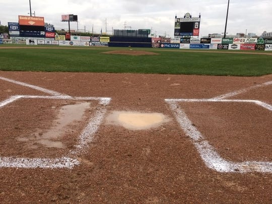 Puddles cover home plate and the right-handed batter's box at Frawley Stadiium after Thursday's DIAA baseball games were called off.