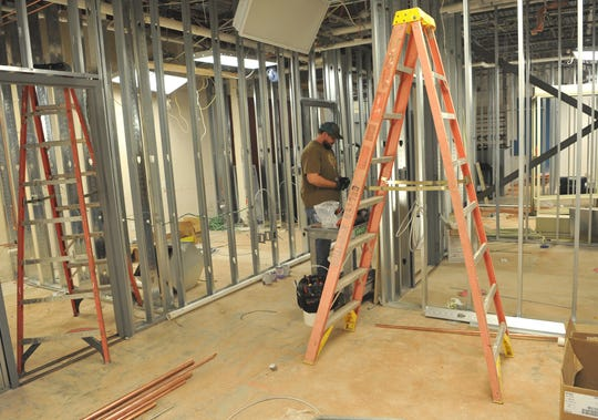 Construction workers work to complete renovations on the Community Healthcare Center's new clinical area, Thursday morning.