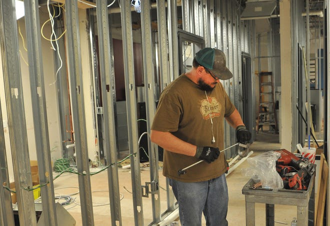 Airco plumber, Chris Ross prepares a piece of all-thread, Thursday morning in preparation of the Community Healthcare Center's new clinical area.