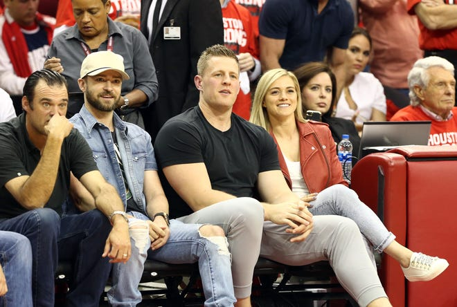 Chicago Red Stars player Kealia Ohai and her boyfriend, Houston Texans defensive end J.J. Watt, sit on the sideline during game five of the Western conference finals of the 2018 NBA Playoffs.