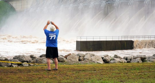 A tourist takes a photo of the water being released from the Keystone Dam above Tulsa, Oklahoma.