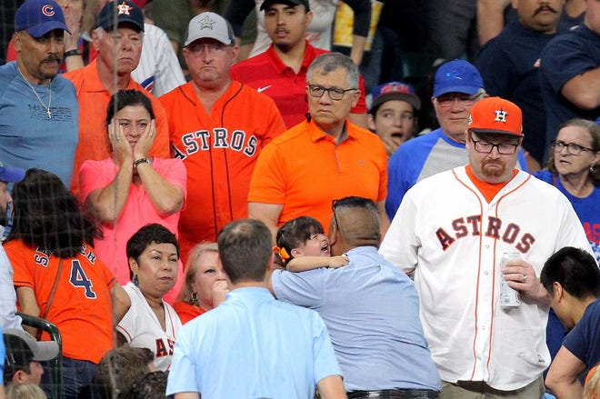 A young fan is taken up to the concourse to receive medical attention after being hit by a foul ball by Chicago Cubs center fielder Albert Almora during the fourth inning against the Houston Astros at Minute Maid Park.