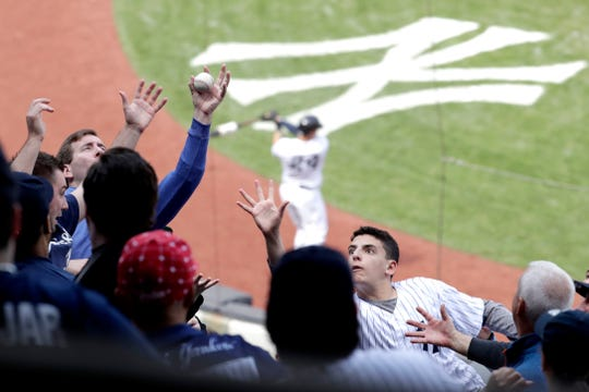A fan barehands a foul ball hit by New York Yankees' Luke Voit during the sixth inning of a baseball game against the Minnesota Twins, Saturday, May 4, 2019, in New York.