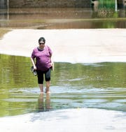Kay Foster, 69, walks barefoot through floodwaters near Tulsa, Oklahoma, after inspecting her daughter's home in the Town & Country  neighborhood.